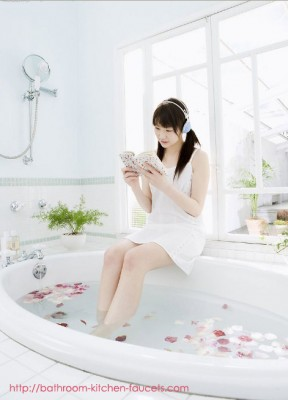 Cute girl reading books in the bathtub